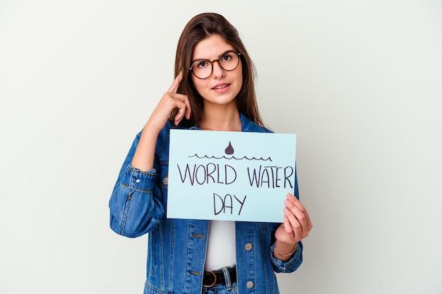 Giovane donna caucasica che celebra la giornata mondiale dell'acqua isolata sul rosa toccando la parte posteriore della testa, pensando e facendo una scelta.