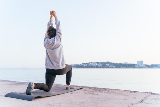 Giovane donna caucasica che fa esercizi di yoga e si allunga al tramonto su una stuoia in riva al mare