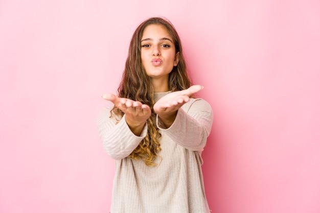 La giovane donna caucasica piega le labbra e tiene i palmi delle mani per inviare un bacio d'aria.