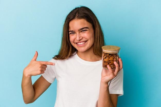Giovane donna caucasica che tiene un barattolo di mandorle isolato su sfondo blu persona che indica a mano uno spazio copia camicia, orgogliosa e fiduciosa