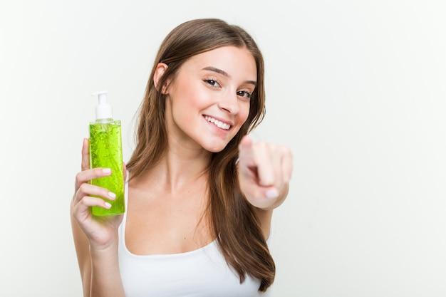 Giovane donna caucasica che tiene una bottiglia di aloe vera sorrisi allegri che indicano la parte anteriore.