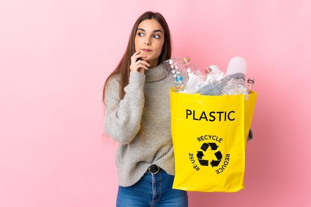 Giovane donna caucasica che tiene un sacchetto pieno di bottiglie di plastica da riciclare isolato su sfondo rosa pensando un'idea mentre cerca