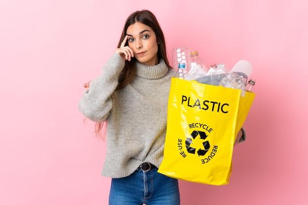 Giovane donna caucasica che tiene un sacchetto pieno di bottiglie di plastica da riciclare isolato su sfondo rosa pensando un'idea