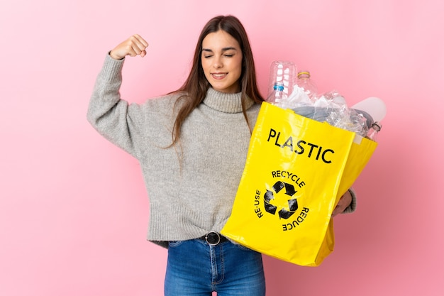 Giovane donna caucasica che tiene un sacchetto pieno di bottiglie di plastica da riciclare isolato su rosa facendo un forte gesto