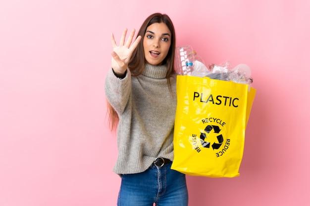Giovane donna caucasica che tiene un sacchetto pieno di bottiglie di plastica da riciclare isolato su rosa felice e contando quattro con le dita