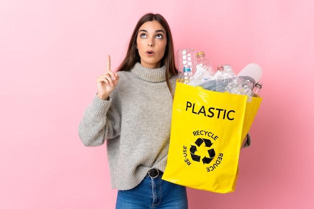 Giovane donna caucasica che tiene un sacchetto pieno di bottiglie di plastica da riciclare isolato su rosa con l'intenzione di realizzare la soluzione mentre si solleva un dito