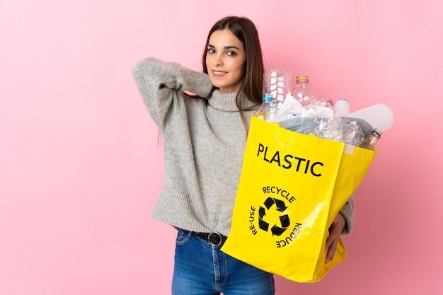 Giovane donna caucasica che tiene un sacchetto pieno di bottiglie di plastica da riciclare isolato sulla risata rosa
