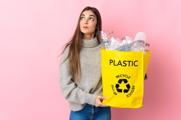 Giovane donna caucasica che tiene un sacchetto pieno di bottiglie di plastica da riciclare isolato sul rosa e alzando lo sguardo