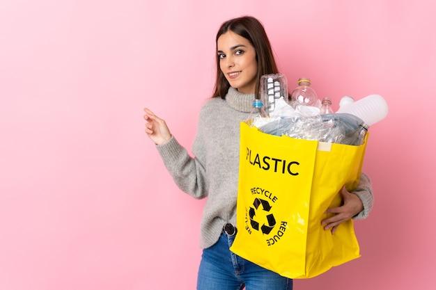 Giovane donna caucasica che tiene un sacchetto pieno di bottiglie di plastica da riciclare isolato su rosa che punta indietro
