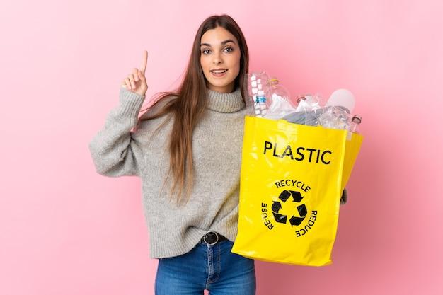 Giovane donna caucasica che tiene un sacchetto pieno di bottiglie di plastica da riciclare isolato sul rosa rivolto verso l'alto una grande idea