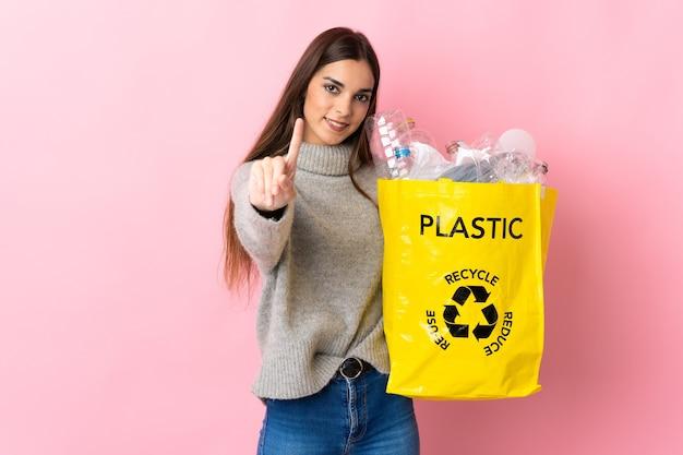 Giovane donna caucasica che tiene un sacchetto pieno di bottiglie di plastica da riciclare isolato sulla rappresentazione rosa e alzando un dito