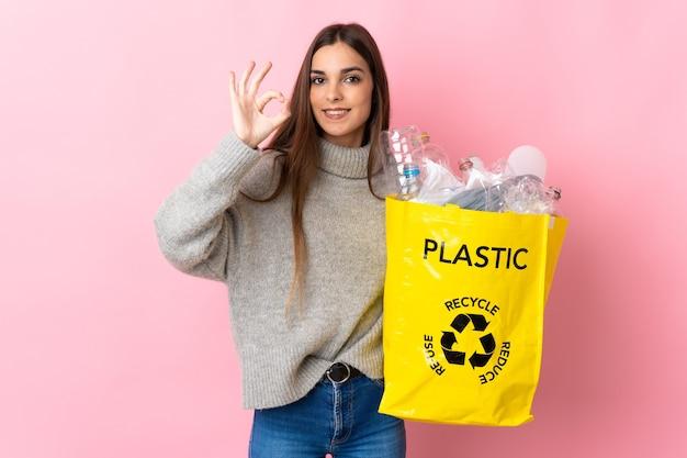 Giovane donna caucasica che tiene un sacchetto pieno di bottiglie di plastica da riciclare isolato sul colore rosa che mostra segno giusto con le dita