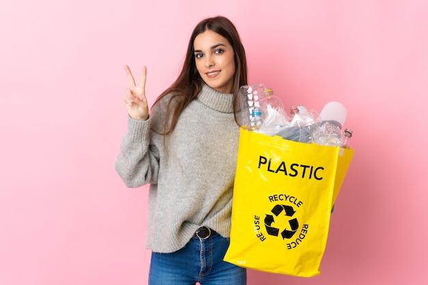 Giovane donna caucasica che tiene un sacchetto pieno di bottiglie di plastica da riciclare isolato su rosa sorridente e mostrando il segno di vittoria