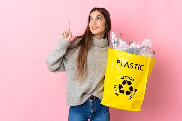 Giovane donna caucasica che tiene una borsa piena di bottiglie di plastica da riciclare sul rosa che indica una grande idea