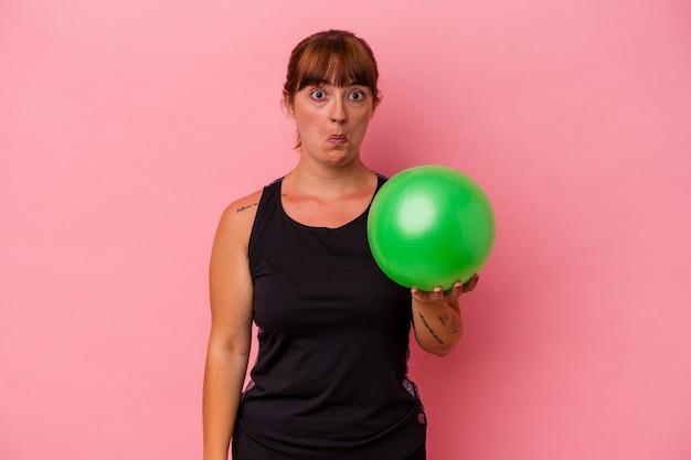 La giovane donna caucasica che tiene la palla per fare sport isolato su sfondo rosa alza le spalle e apre gli occhi confusi.