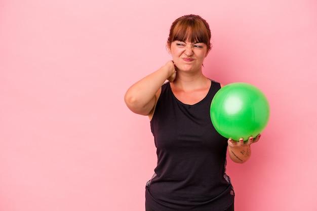 Giovane donna caucasica che tiene la palla per fare sport isolato su sfondo rosa toccando la nuca, pensando e facendo una scelta.