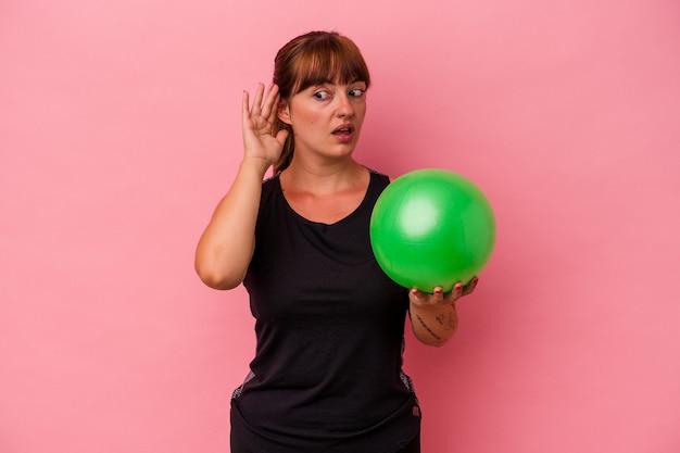 Giovane donna caucasica che tiene la palla per fare sport isolato su sfondo rosa cercando di ascoltare un pettegolezzo.