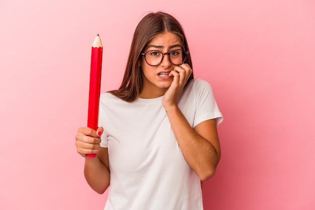 Giovane donna caucasica in possesso di una grande matita isolata su sfondo rosa che si morde le unghie, nervosa e molto ansiosa.
