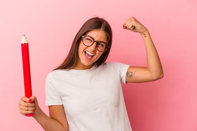 Giovane donna caucasica che tiene una grande matita isolata su fondo rosa che alza il pugno dopo una vittoria, concetto del vincitore.