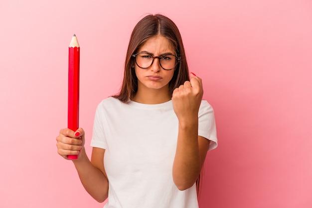 Giovane donna caucasica che tiene in mano una grande matita isolata su sfondo rosa che mostra il pugno alla telecamera, espressione facciale aggressiva.