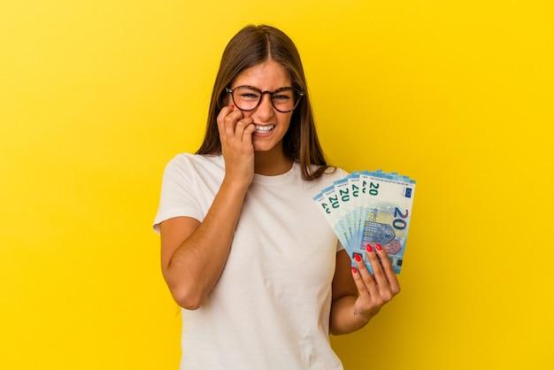 Giovane donna caucasica con banconote isolate su sfondo giallo che si mordono le unghie, nervosa e molto ansiosa.