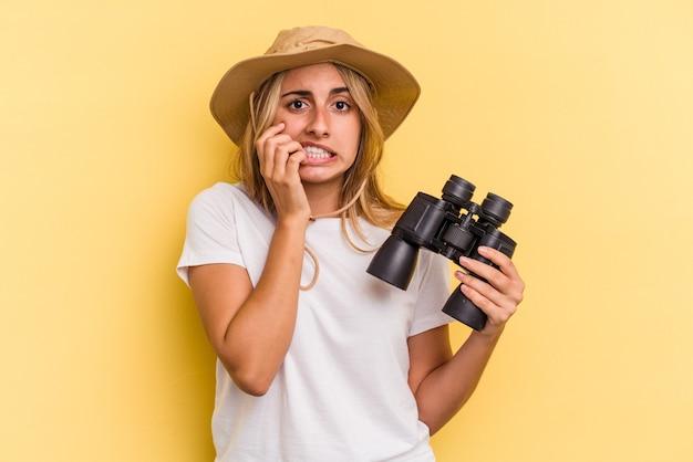 Giovane donna caucasica che tiene in mano un binocolo isolato su sfondo giallo che si morde le unghie, nervoso e molto ansioso.