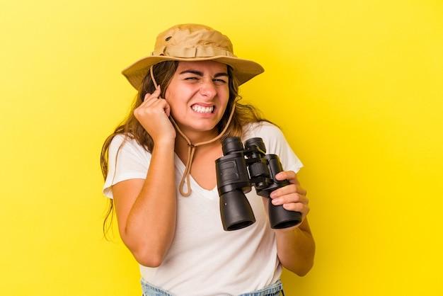 Giovane donna caucasica che tiene il binocolo isolato su sfondo giallo che copre le orecchie con le mani.