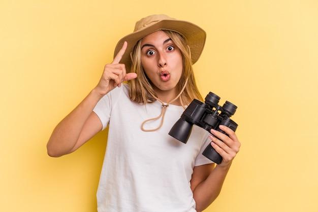 Giovane donna caucasica che tiene il binocolo isolato su sfondo giallo avente un'idea, concetto di ispirazione.