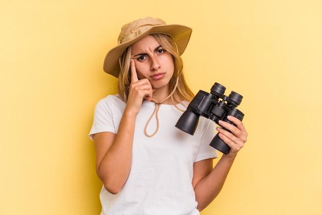 Giovane donna caucasica che tiene il binocolo isolato su sfondo giallo che punta il tempio con il dito, pensando, concentrato su un compito.