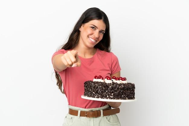 Giovane donna caucasica che tiene la torta di compleanno isolata su fondo bianco che indica la parte anteriore con l'espressione felice