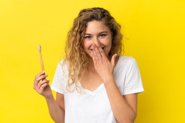 Giovane donna caucasica che tiene in mano un lavarsi i denti isolato su sfondo giallo felice e sorridente che copre la bocca con la mano