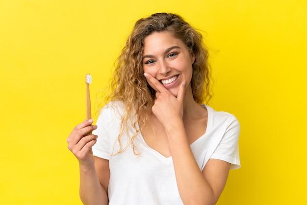Giovane donna caucasica che tiene un lavarsi i denti isolato su sfondo giallo felice e sorridente