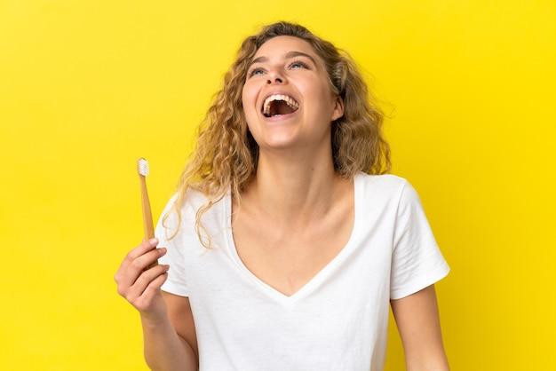 Giovane donna caucasica che tiene un lavarsi i denti isolato su sfondo giallo ridendo