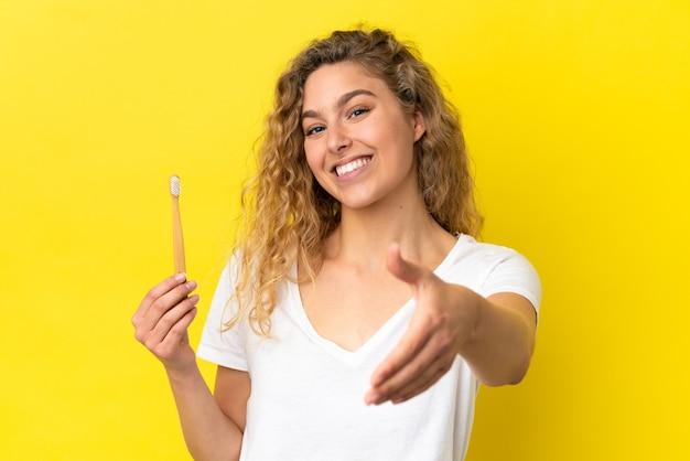 Giovane donna caucasica che tiene in mano un lavarsi i denti isolato su sfondo giallo che stringe la mano per chiudere un buon affare