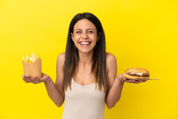 Giovane donna caucasica che tiene hamburger e patatine isolati su sfondo giallo