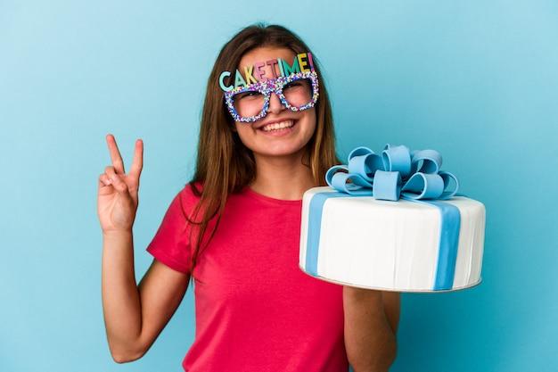 Giovane donna caucasica che tiene una torta isolata su sfondo blu che mostra il numero due con le dita.