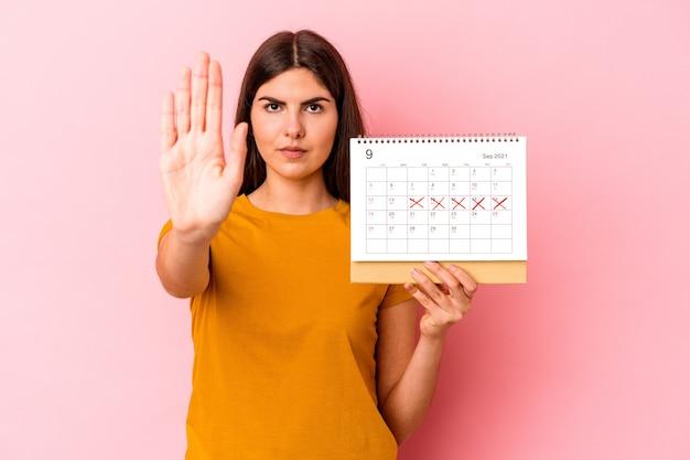 Giovane donna caucasica che tiene il calendario isolato su sfondo rosa in piedi con la mano tesa che mostra il segnale di stop, impedendoti.