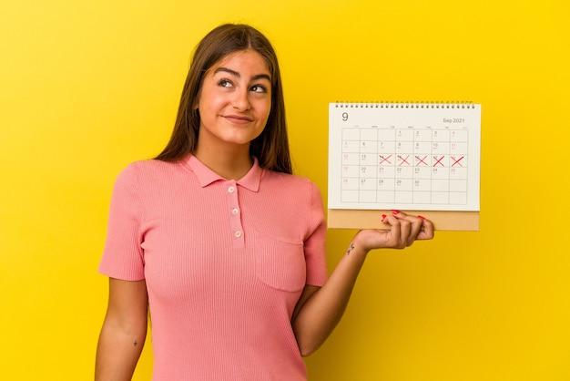Giovane donna caucasica in possesso di un calendario isolato su sfondo giallo che sogna di raggiungere obiettivi e scopi