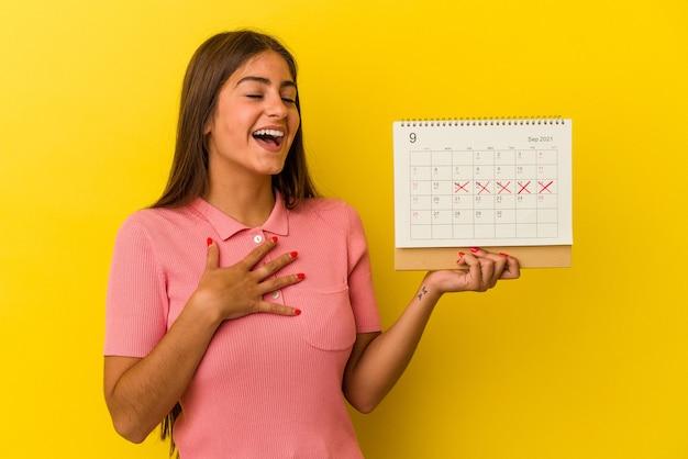 La giovane donna caucasica che tiene un calendario isolato su sfondo giallo ride forte tenendo la mano sul petto.
