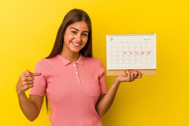 Giovane donna caucasica in possesso di un calendario isolato su sfondo giallo persona che indica a mano uno spazio copia camicia, orgogliosa e fiduciosa
