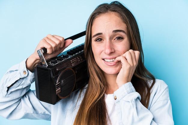 Giovane donna caucasica che tiene un cassete isolato unghie mordaci, nervose e molto ansiose.