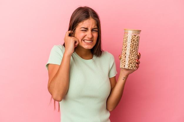 Giovane donna caucasica che tiene un barattolo di ceci isolato su sfondo rosa che copre le orecchie con le mani.