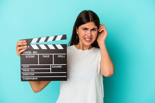 Giovane donna caucasica che tiene un ciak isolato su sfondo blu che copre le orecchie con le mani.