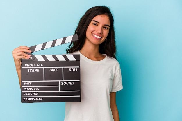 Giovane donna caucasica che tiene un ciak isolato su sfondo blu felice, sorridente e allegro.