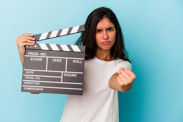 Giovane donna caucasica che tiene un ciak isolato su sfondo blu che mostra il pugno alla telecamera, espressione facciale aggressiva.