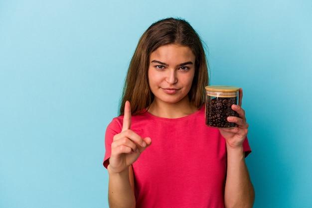 Giovane donna caucasica che tiene un barattolo di caffè isolato su sfondo blu che mostra il numero uno con il dito.
