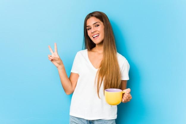 Giovane donna caucasica che tiene una tazza da caffè allegra e spensierata mostrando un simbolo di pace con le dita.