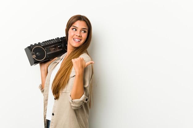 La giovane donna caucasica che tiene un blaster guetto punta con il pollice lontano, ridendo e spensierata.