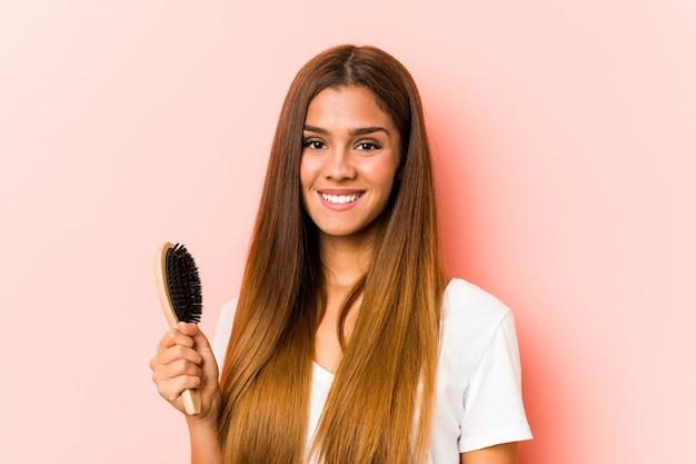 Giovane donna caucasica che tiene una spazzola per capelli felice, sorridente e allegra.