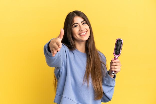 Giovane donna caucasica che tiene la spazzola per capelli isolata su fondo blu che stringe la mano per chiudere un buon affare